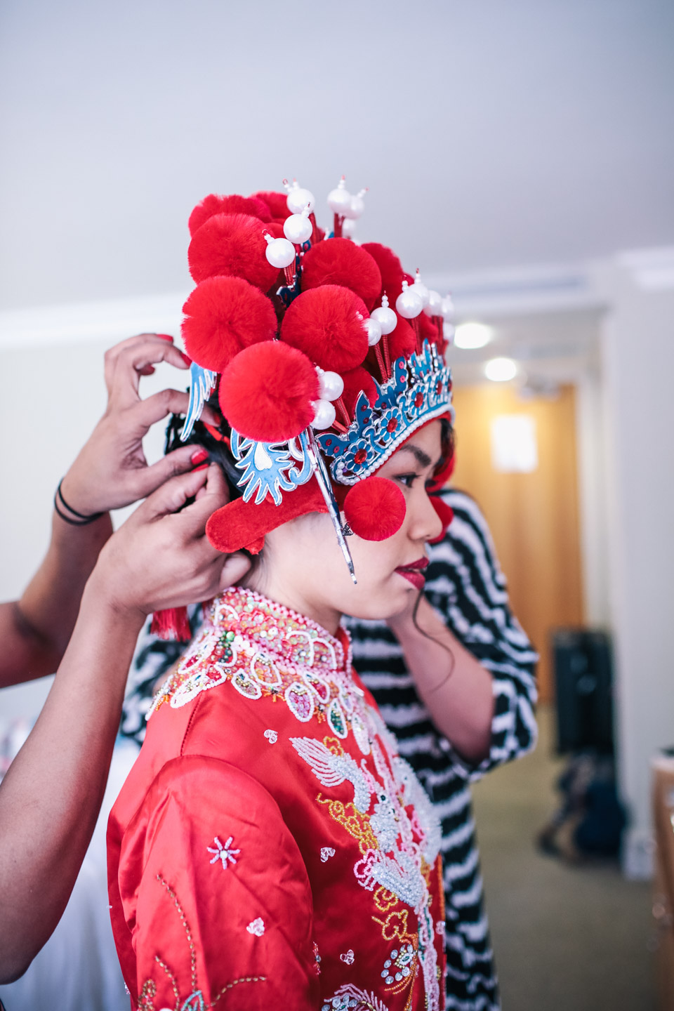 chinese bride putting her head dress on