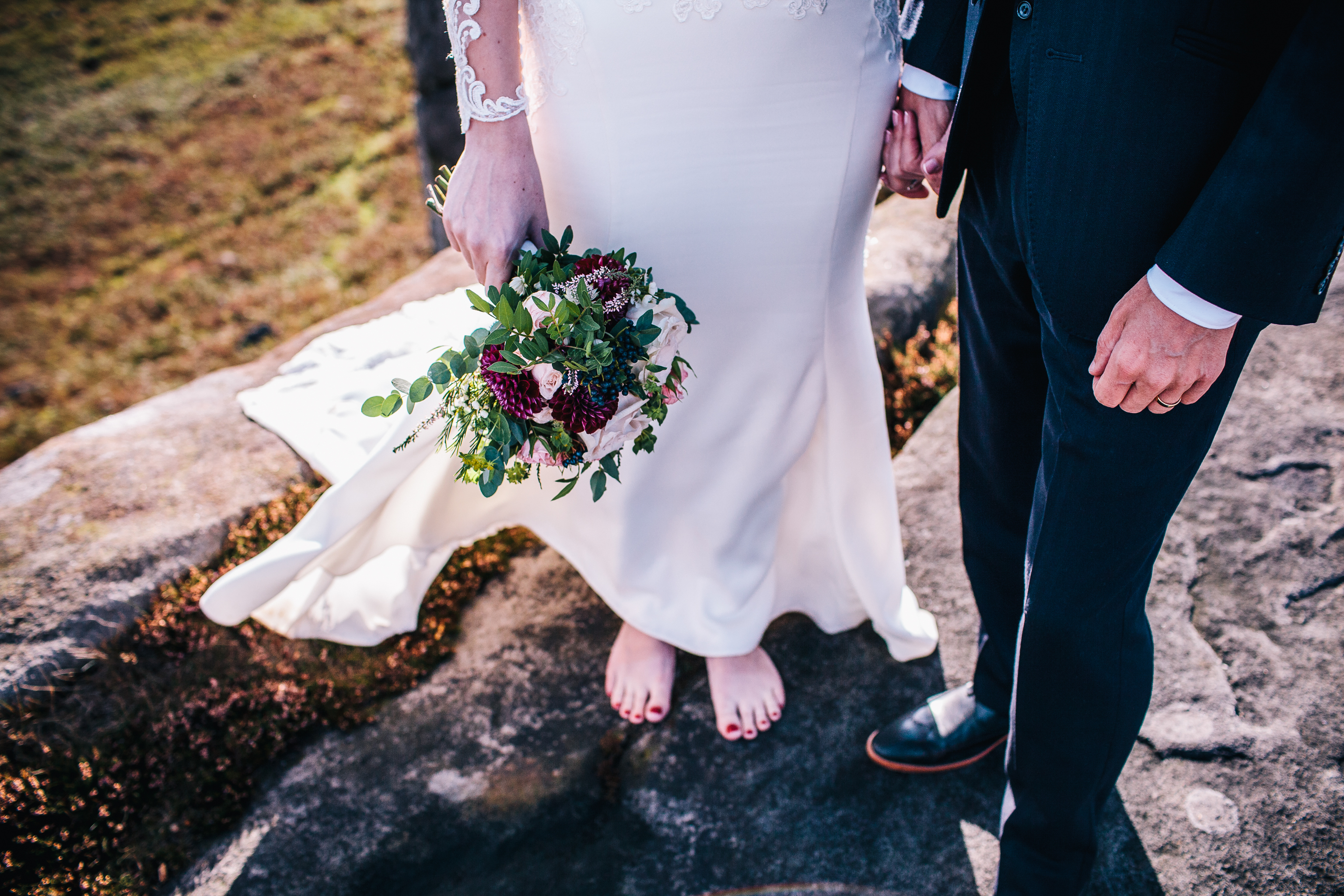 bride standing in bare feet on a rock in peak district