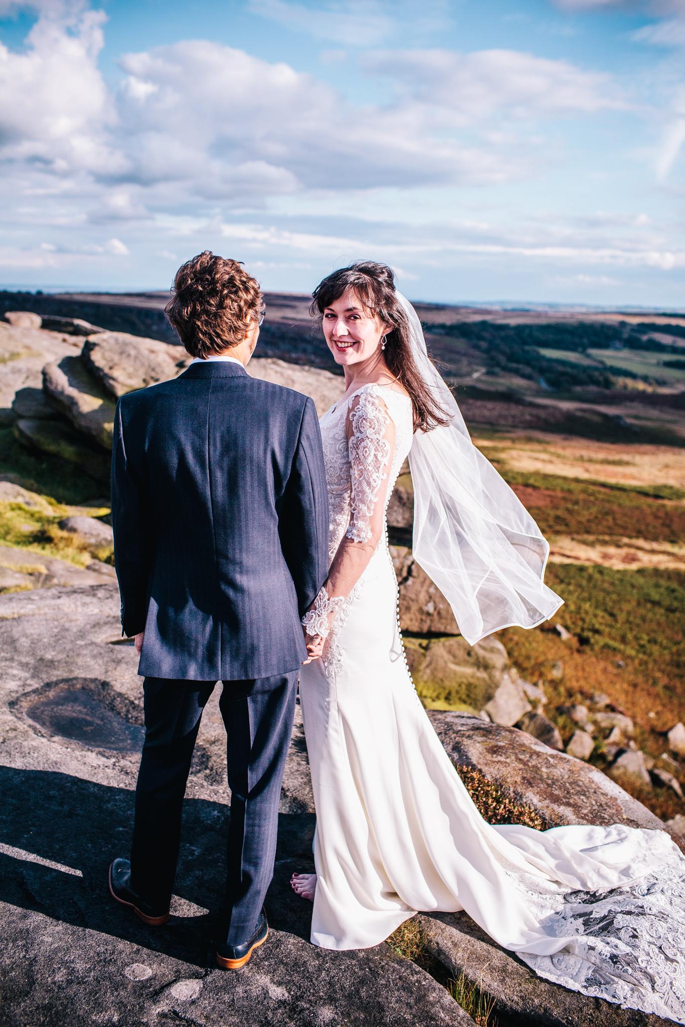 bride looking over shoulder towards camera int he Peak District