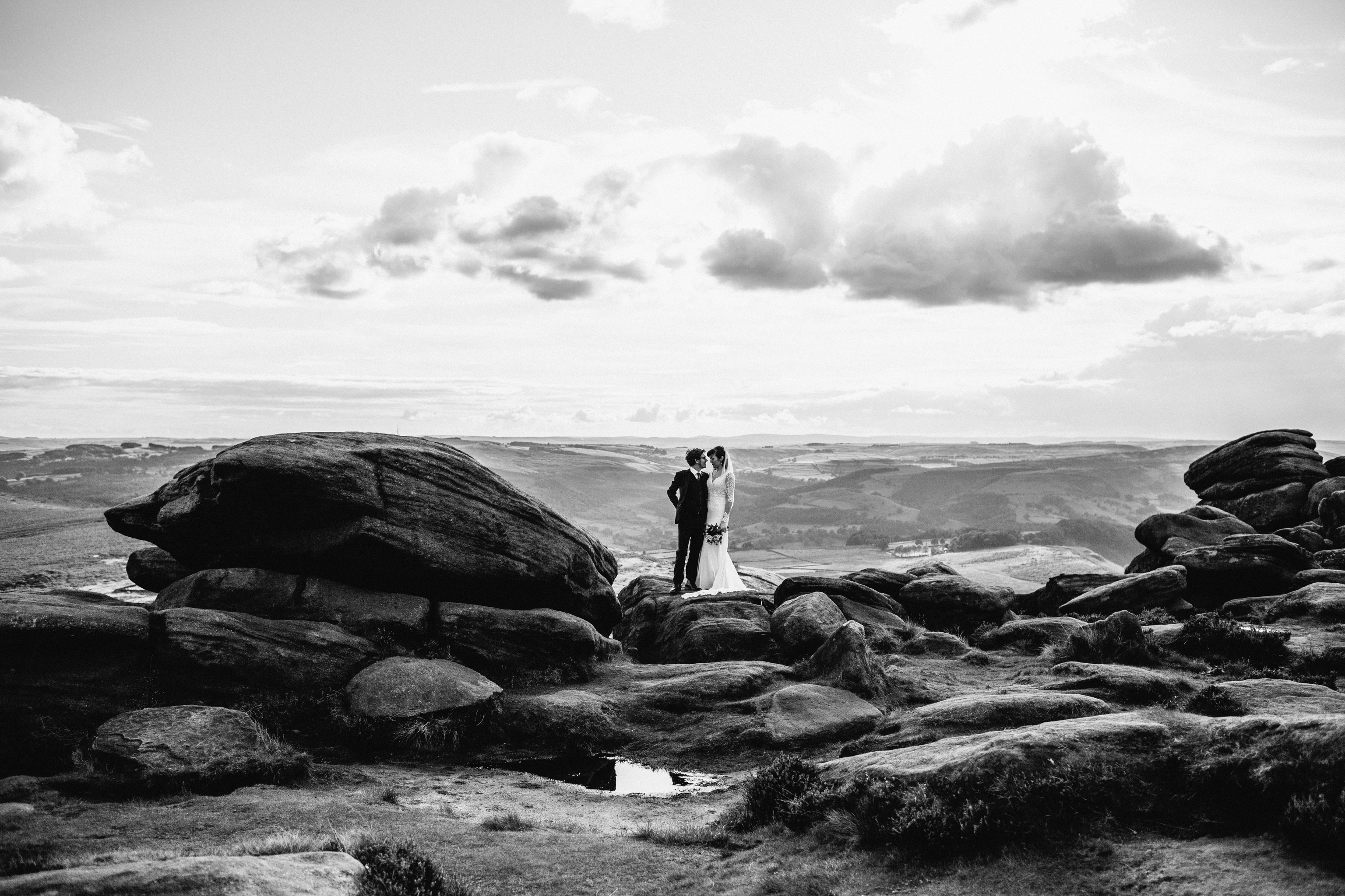 epic photo of wedding couple standing together on top of a rock