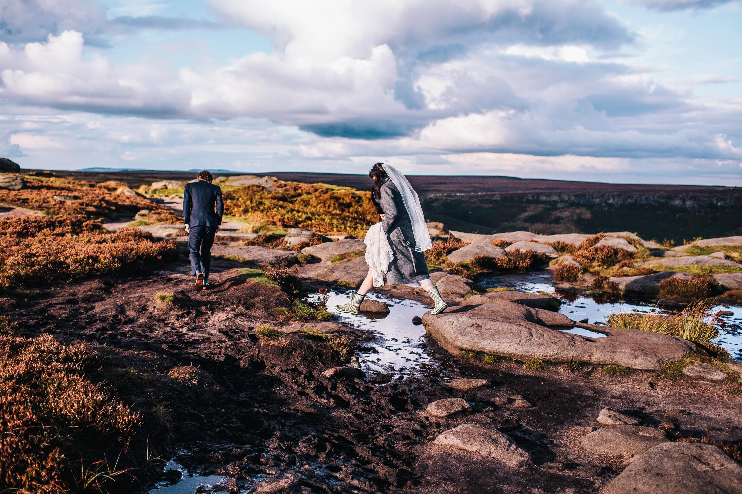 bride jumping over rocks at peak district