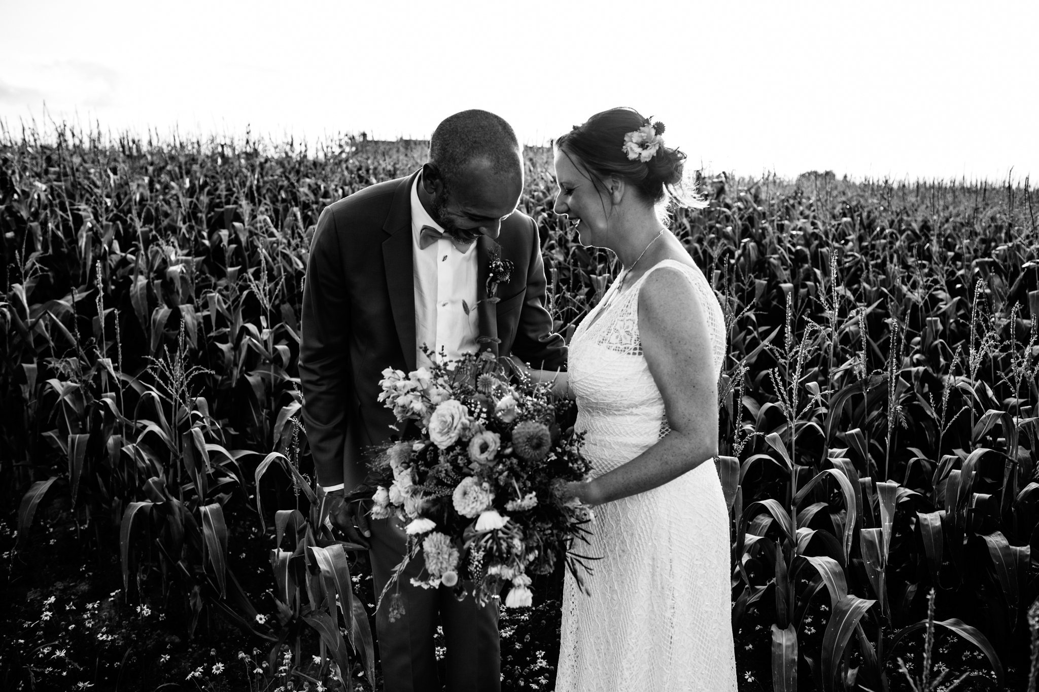 alternative colourful wedding at Seymours court with couple laughing in corn field