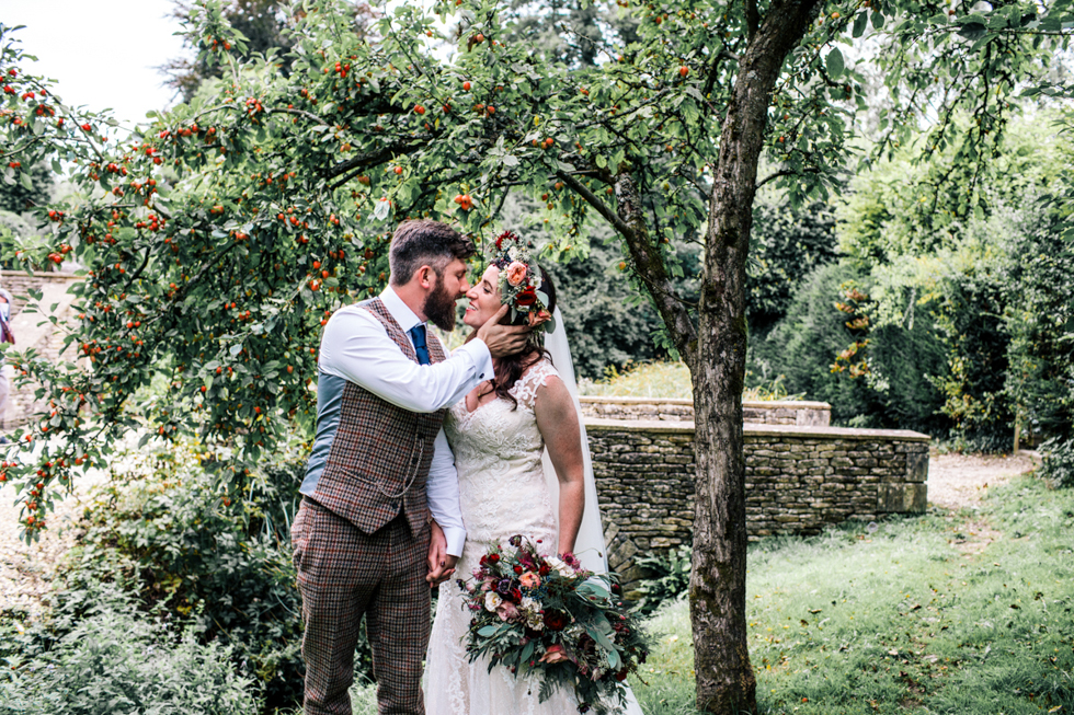 bride and groom portrait session under an apple tree outdoors at Owlpen Manor Festival Wedding