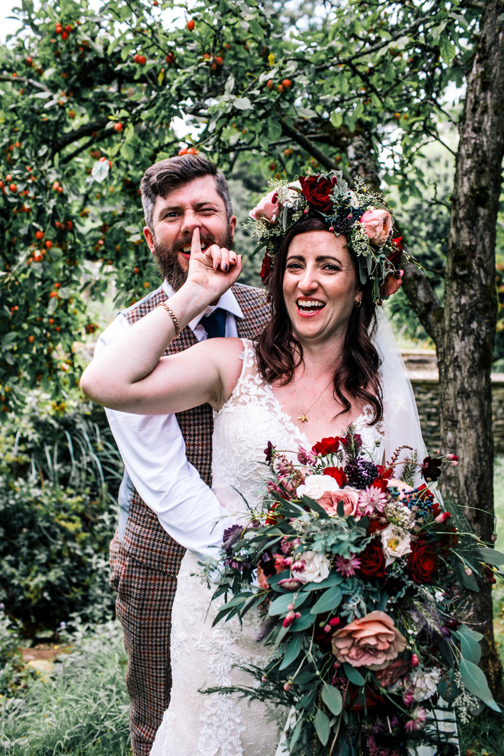 bride sticking her finger up grooms nose at quirky fun festival wedding at Owlpen Manor