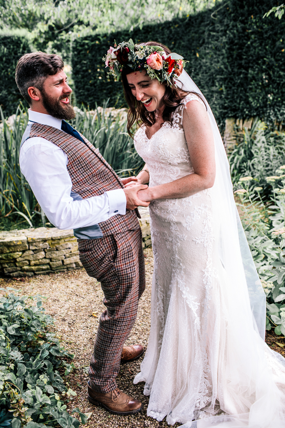 quirky bride and groom laughing together during couple portraits outside at Owlpen Manor