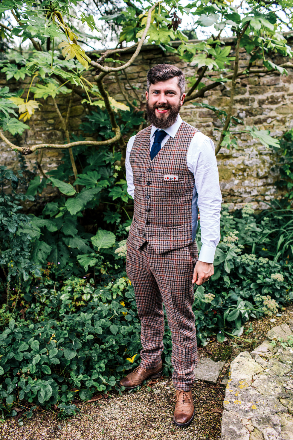 Groom looking dapper in three piece tweed check suit outside at Owlpen Manor
