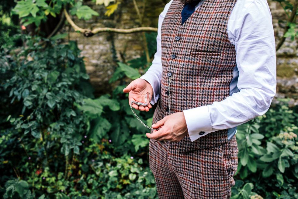Groom looking dapper in three piece tweed check suit outside at Owlpen Manor with a pocket watch in his hand