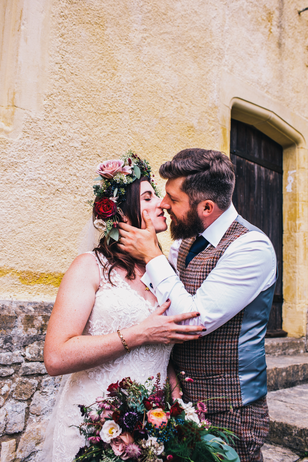 quirky bride and groom kissing against yellow stone wall at Owlpen Manor