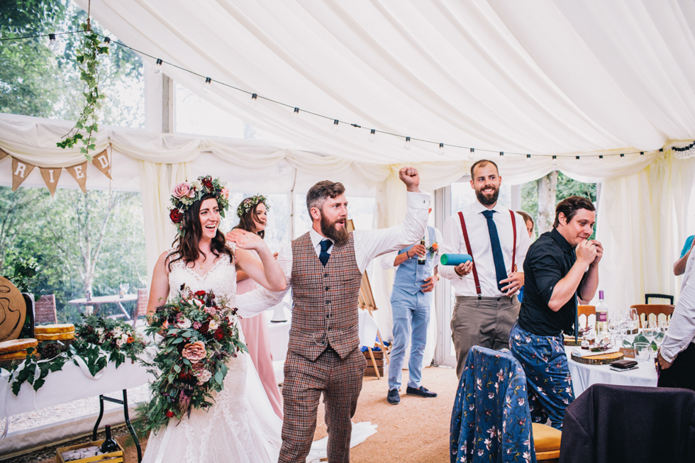 quirky bride and groom entering the wedding reception in style together laughing and having fun at Owlpen manor