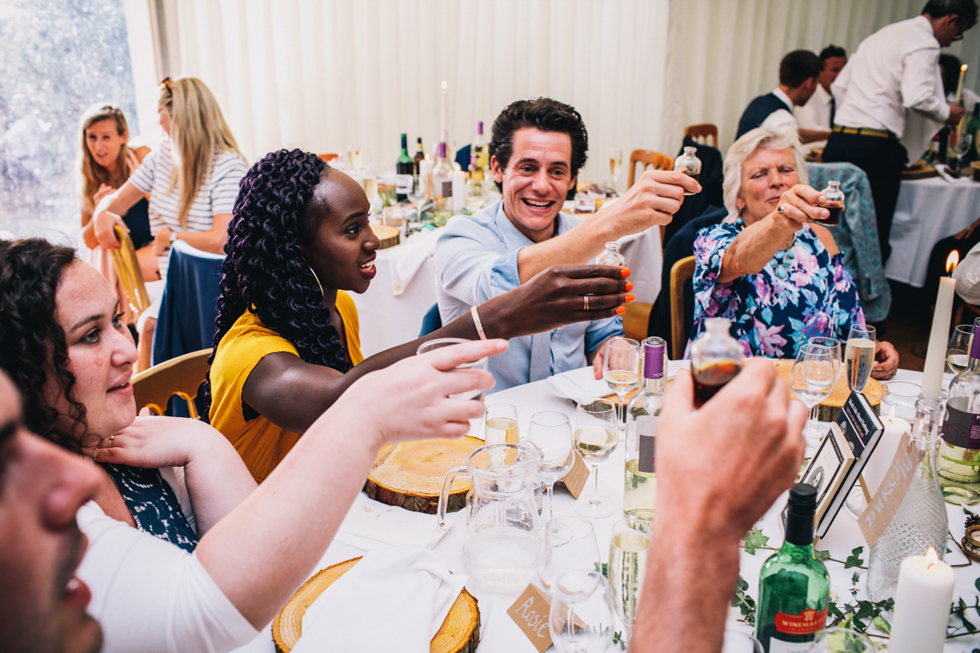 wedding guests doing shots of home made slow gin