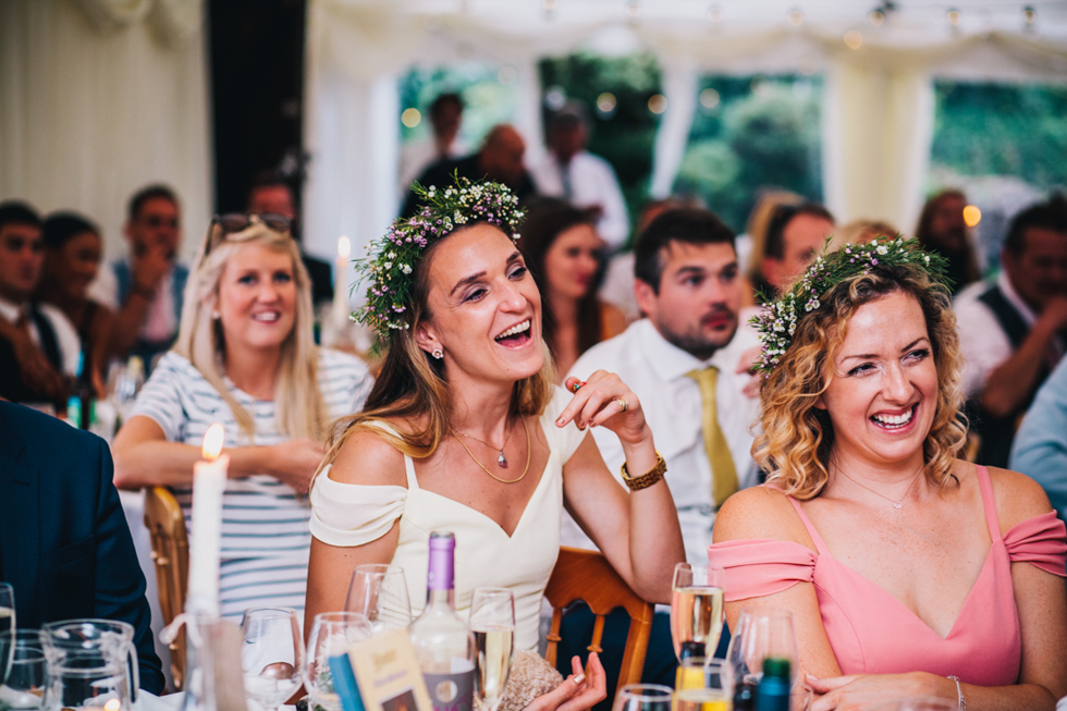 bridesmaids laughing at wedding speeches at quirky outdoor wedding at Owlpen Manor