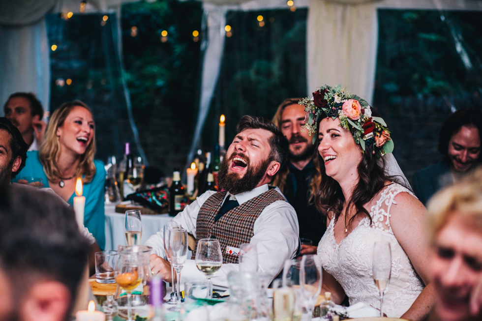 bride and groom laughing at their wedding speeches at Owlpen Manor festival themed wedding