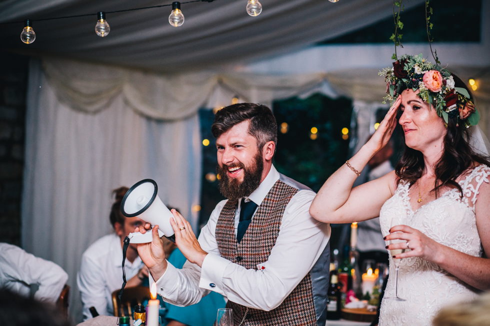 groom doing his speech with a megaphone and laughing