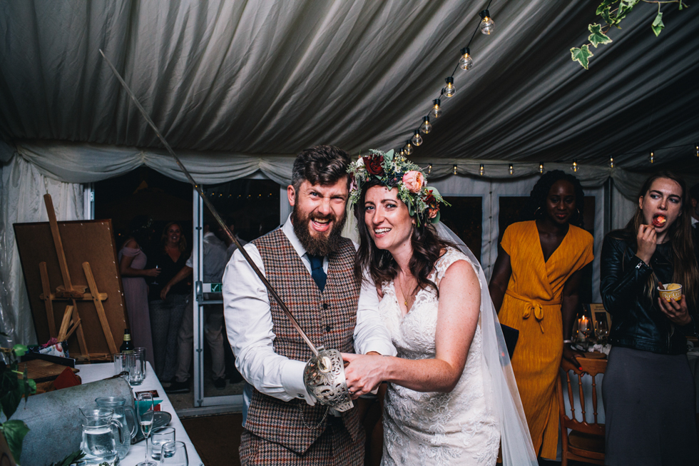 quirky fun bride and groom cutting the cake with a huge sword