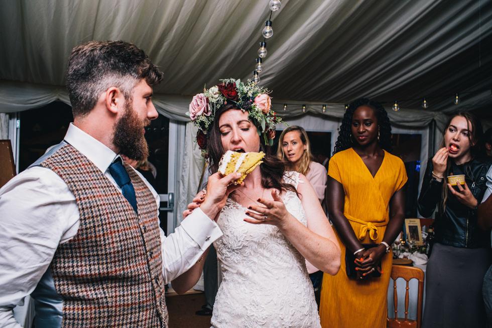 groom feeding bride a huge piece of Victoria sponge cake