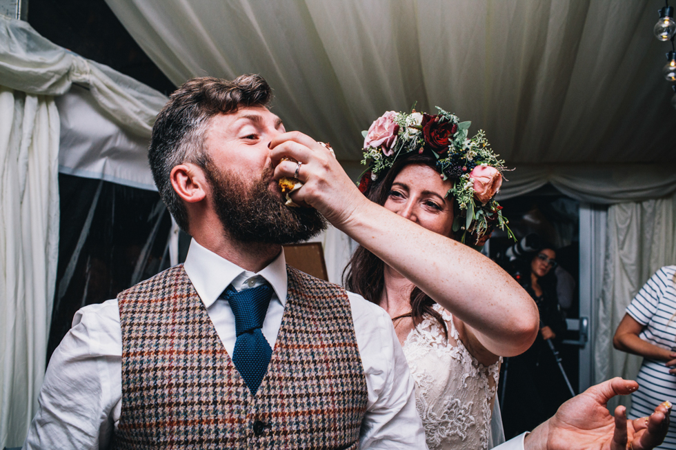 bride shoving cake into grooms face at fun filled festival wedding at Owlpen Manor