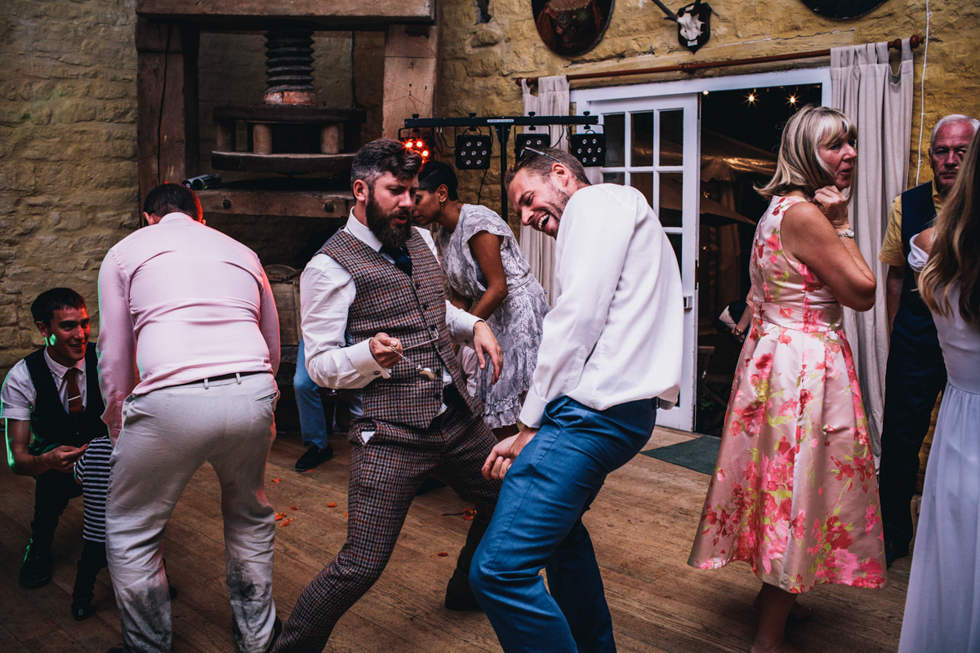 drunk wedding guests making funny shapes on the dance floor at the end of night
