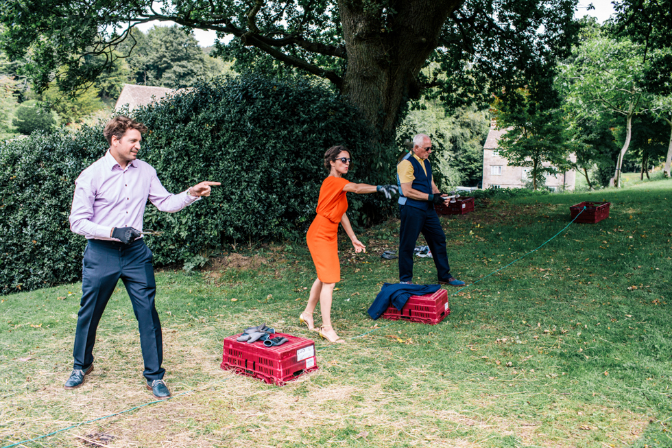 fun alternative quirky bride and groom taking part in the axe throwing competition at Owlpen Manor festival wedding