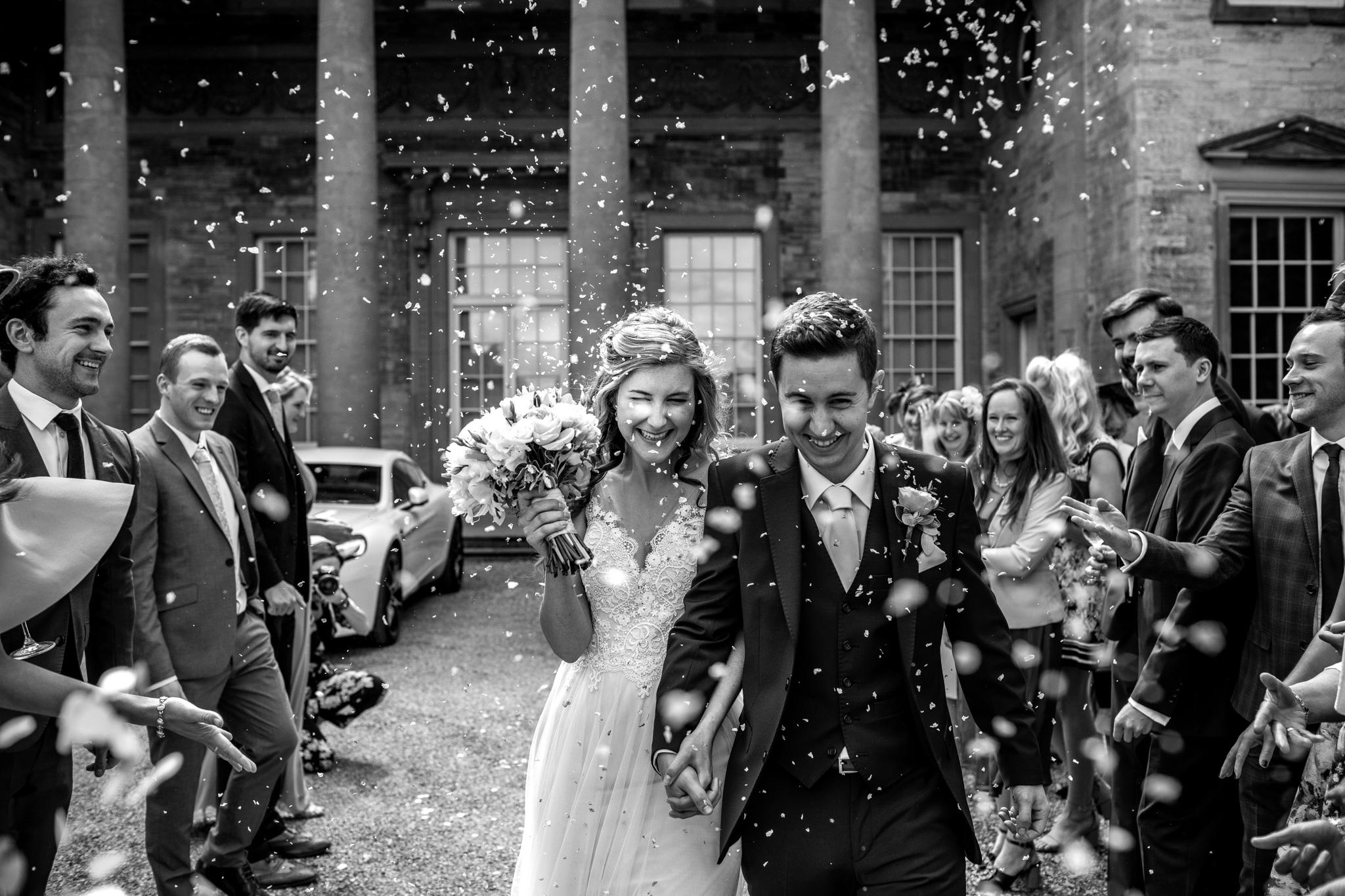 Compton Verney wedding couple walking through confetti