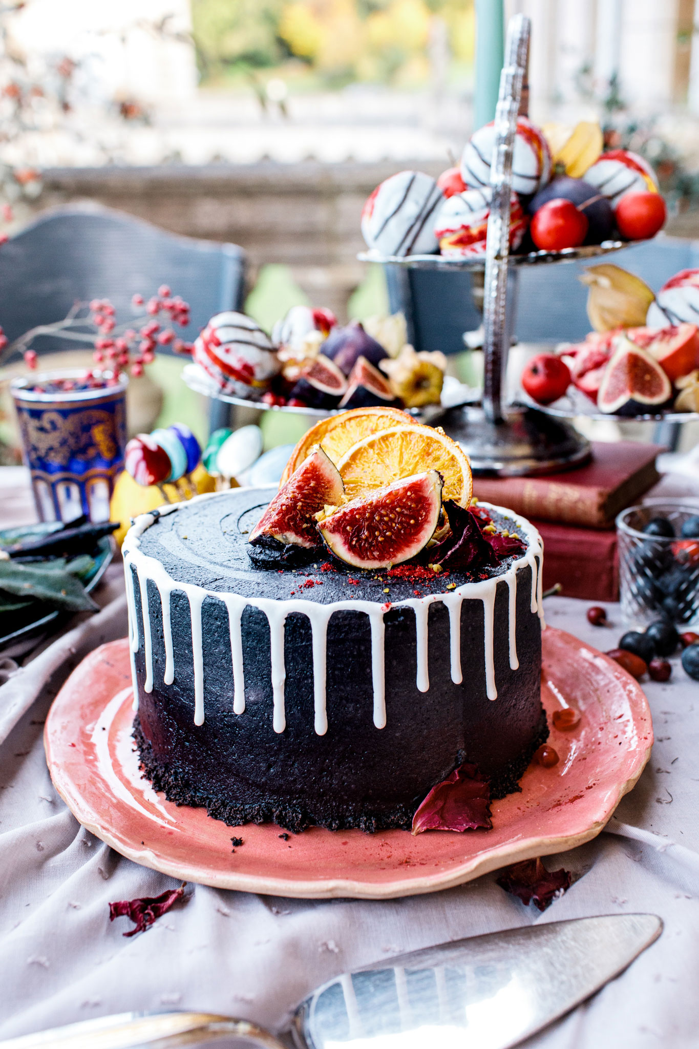 black vegan wedding cake with figs and icing dripping down