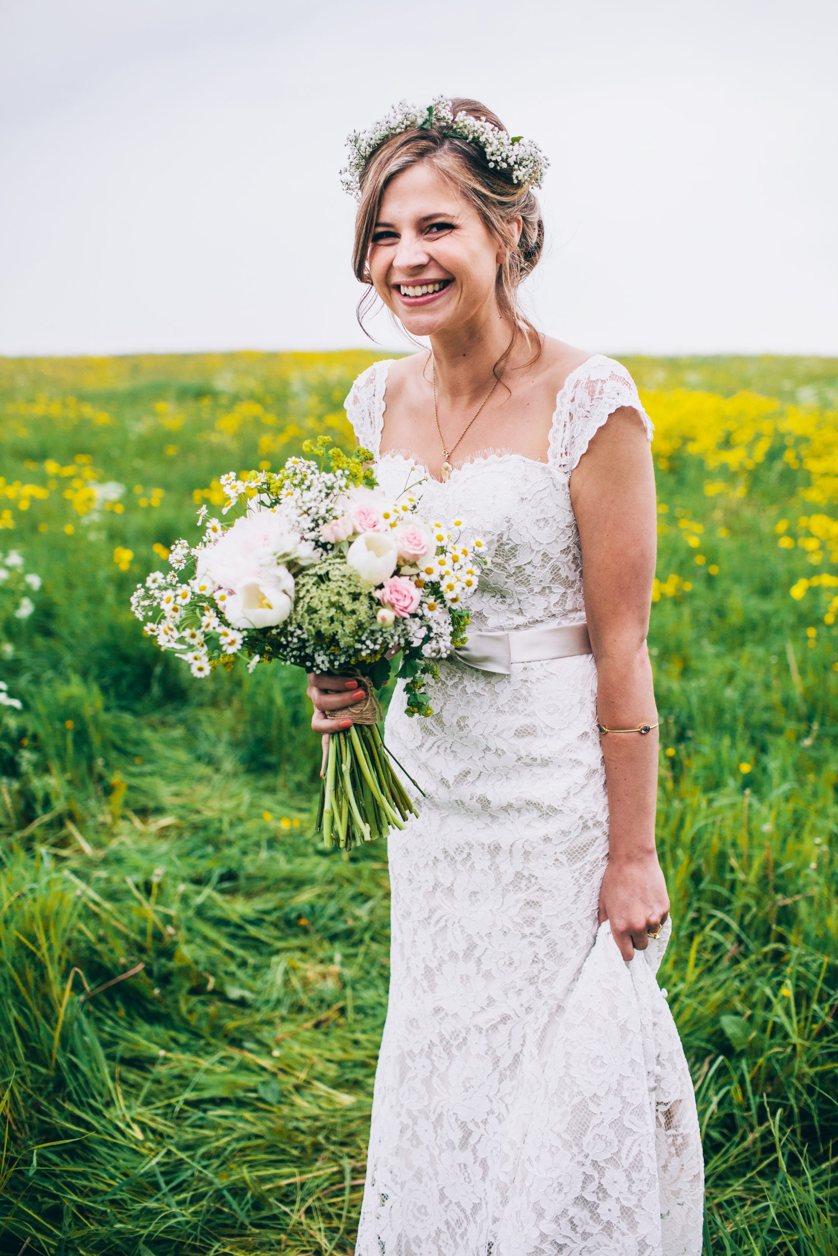happy bride standing in yellow field at Cripps barn cotswold smiling