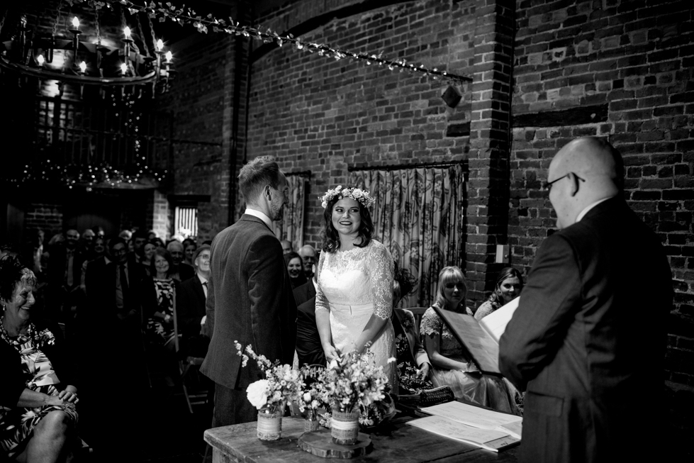 bride smiling at groom whilst they exchange vows at the Curradine Barns