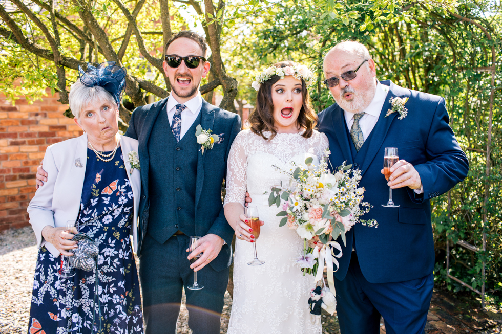 brides parents pulling funny faces in their group shots at Curradine Barns