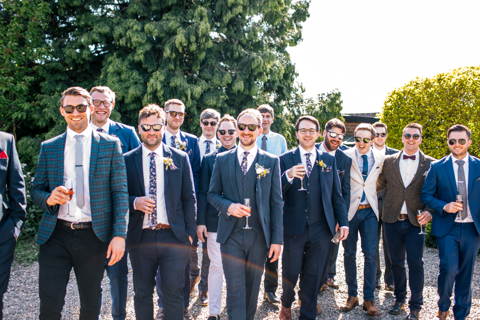 groom and all his mates walking in the sunshine at Curradine Barns