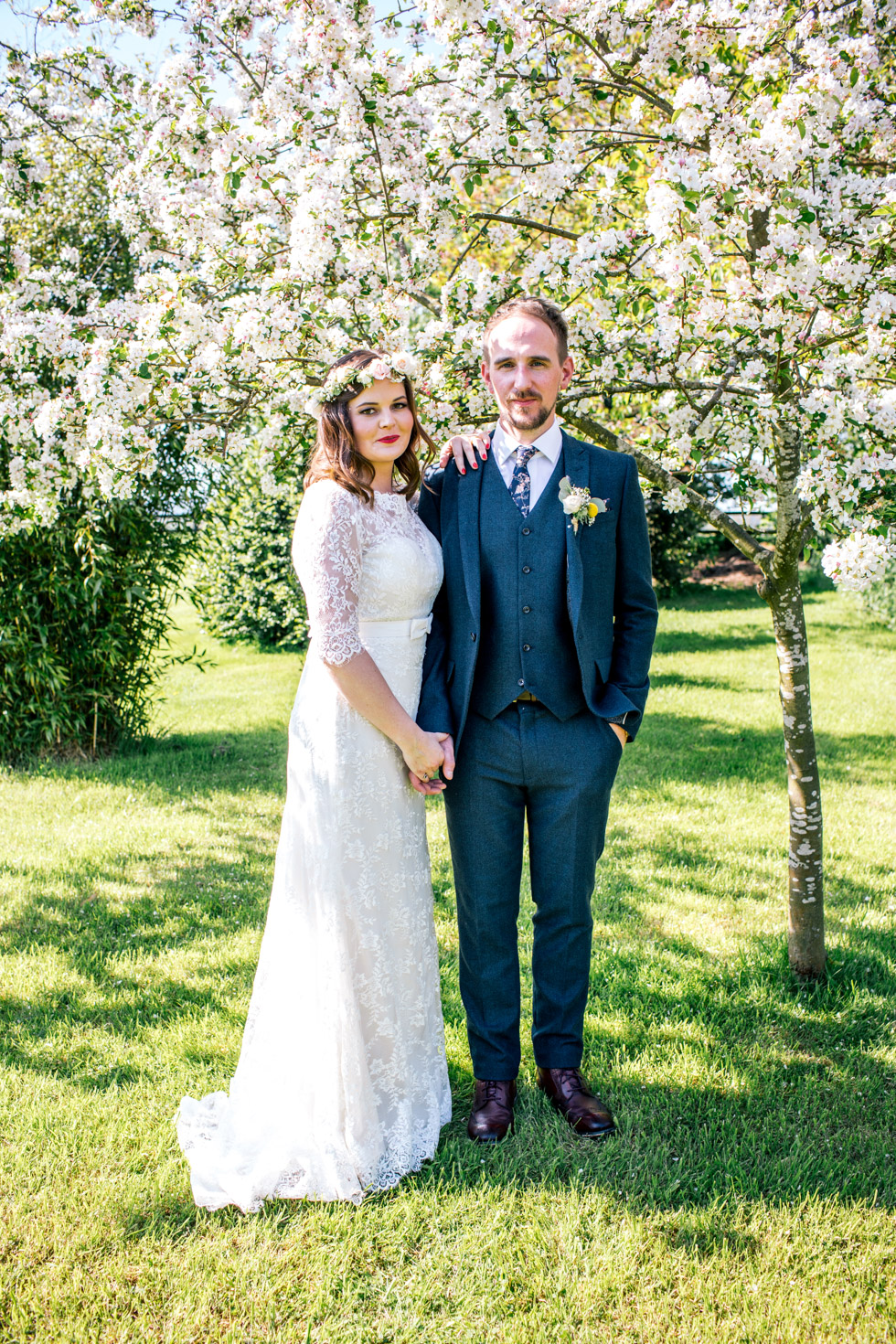 bride and groom standing in spring confetti trees at the curradine barns