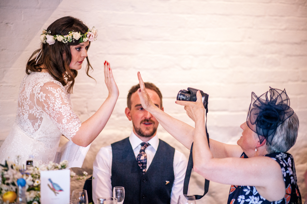 bride giving her mum a high five after she finished her wedding speech