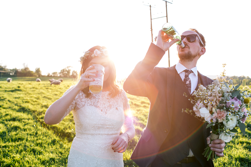 bride and groom downing a pint of ale in the sun at the Curradine Barns