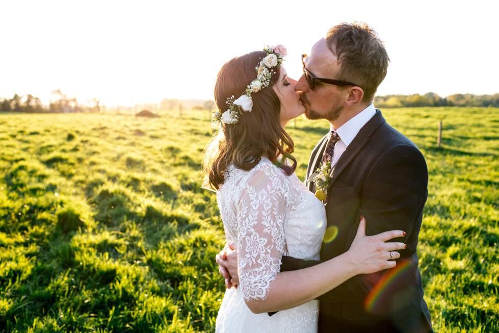 alternative bride and groom kissing in the sun with a rainbow in the background