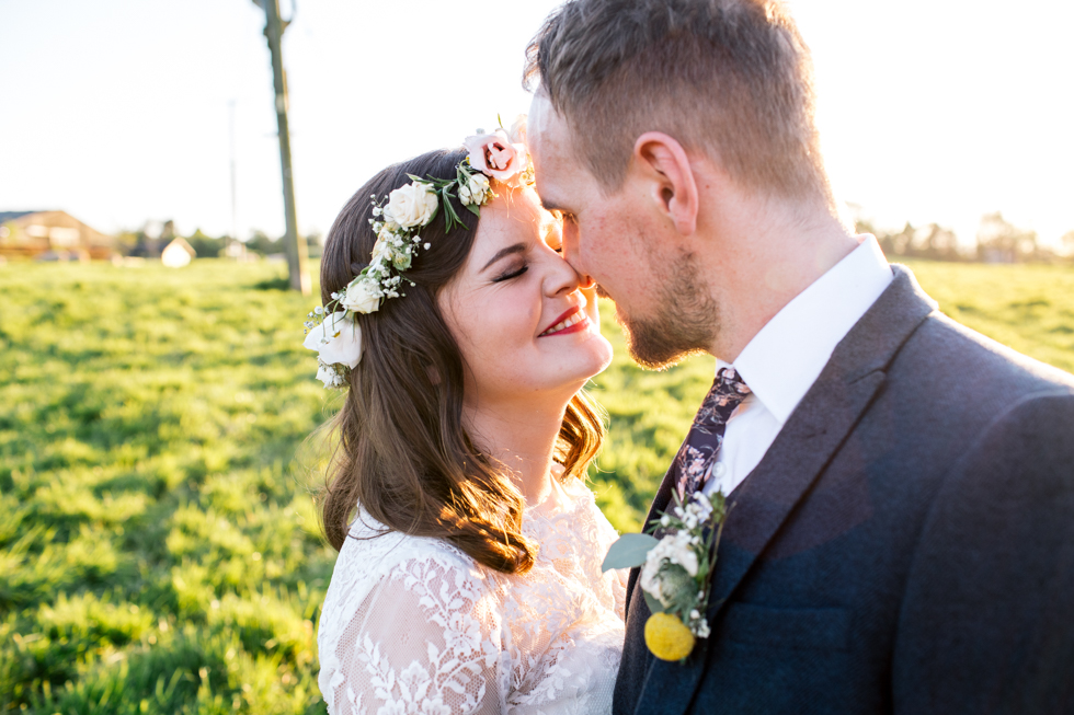 unique bride wearing floral crown and glamorous lace dress standing in the sunshine with her groom