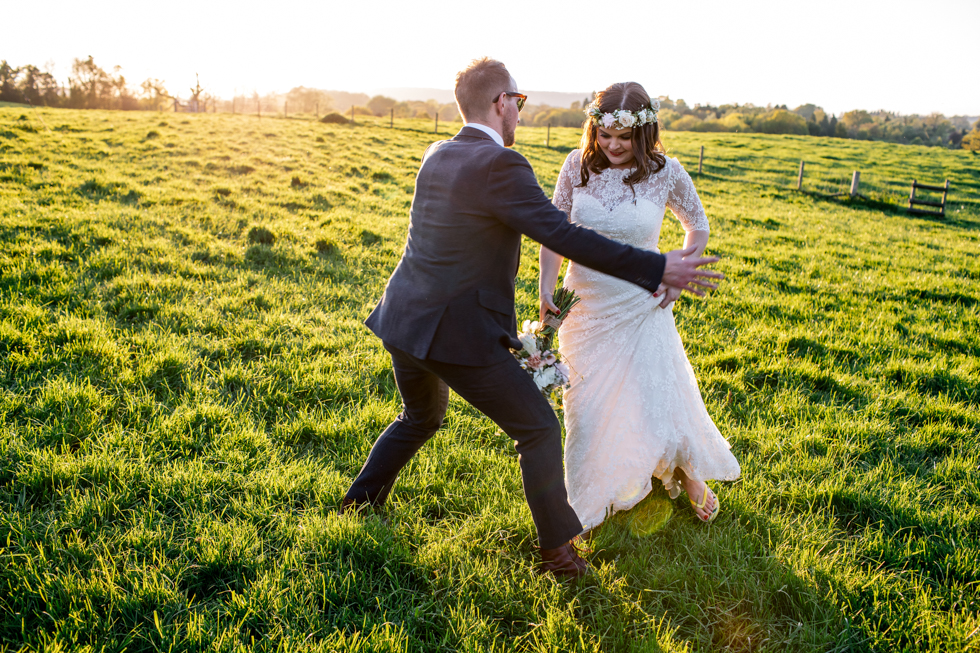 fun bride and groom messing about in a field for their photo's with the sunshine in the background