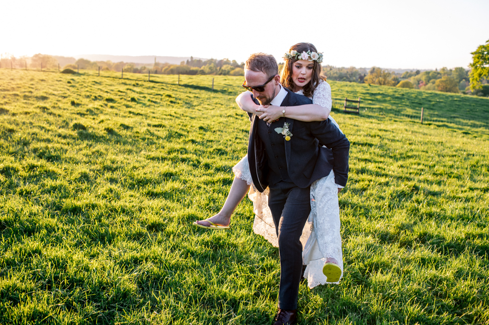 groom giving the bride a piggy back in the blazing sunshine after just getting married