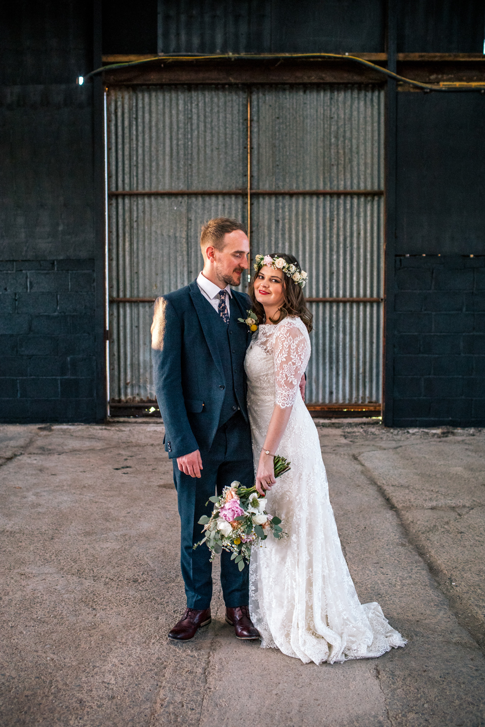 unique couple with bride dressed in layered lace dress standing in the middle of a deserted cow shed for their evening couple portraits