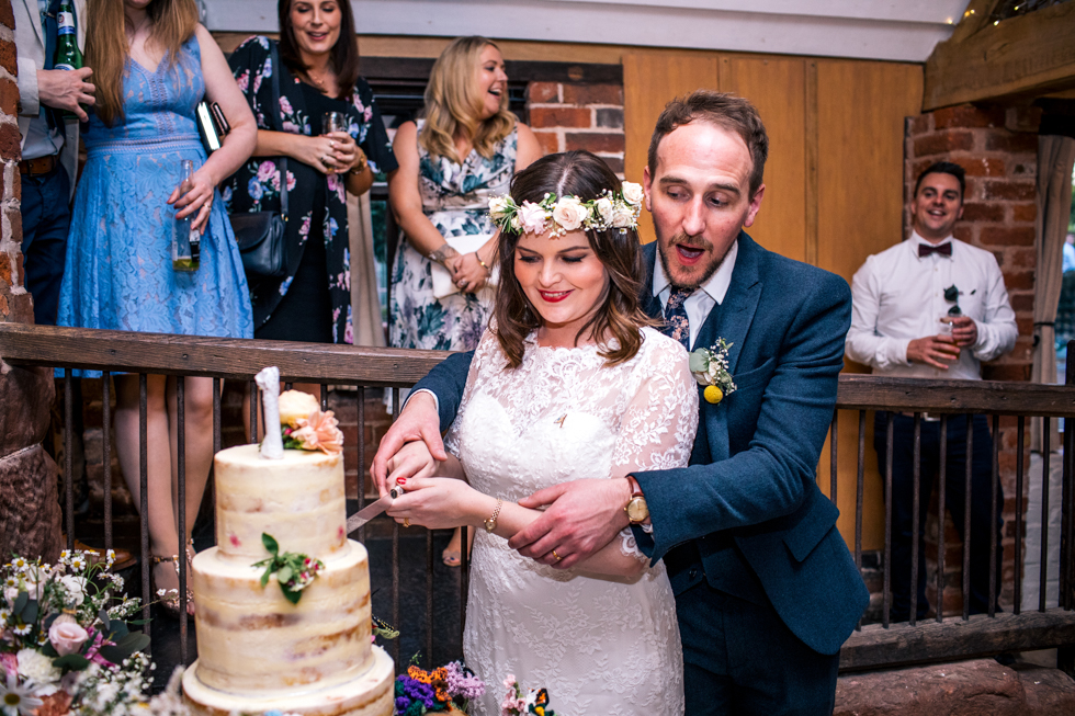 bride and groom cutting their massive home made naked cake
