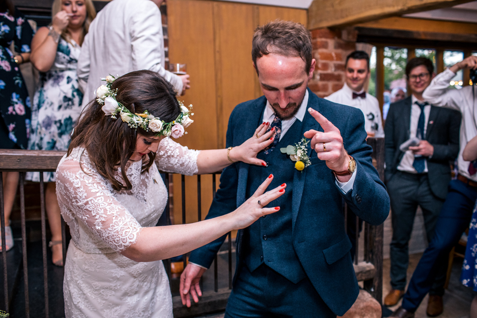 bride feeding wedding cake to groom by shoving it in his face