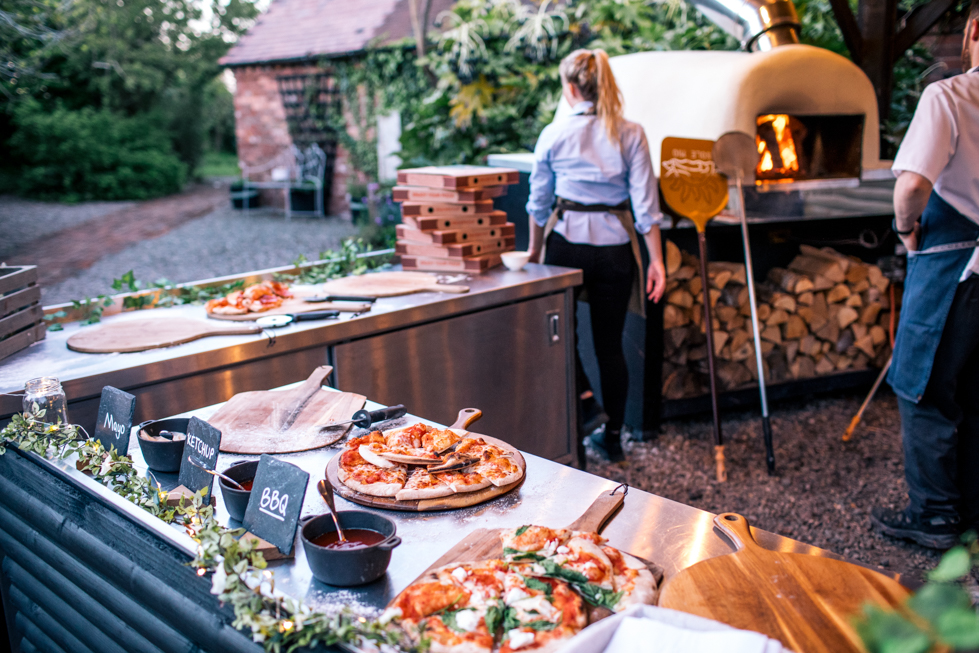 pizza being cooked on wooden oven outside for rustic wedding at the Curradine Barns