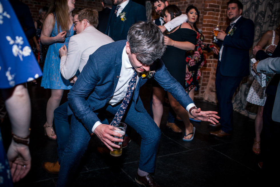 wedding guests dancing and making shapes and going crazy on the dance floor