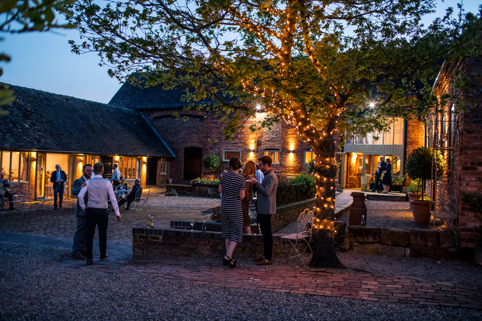 Curradine Barns at night outside with their courtyard all lit up with fairy lights