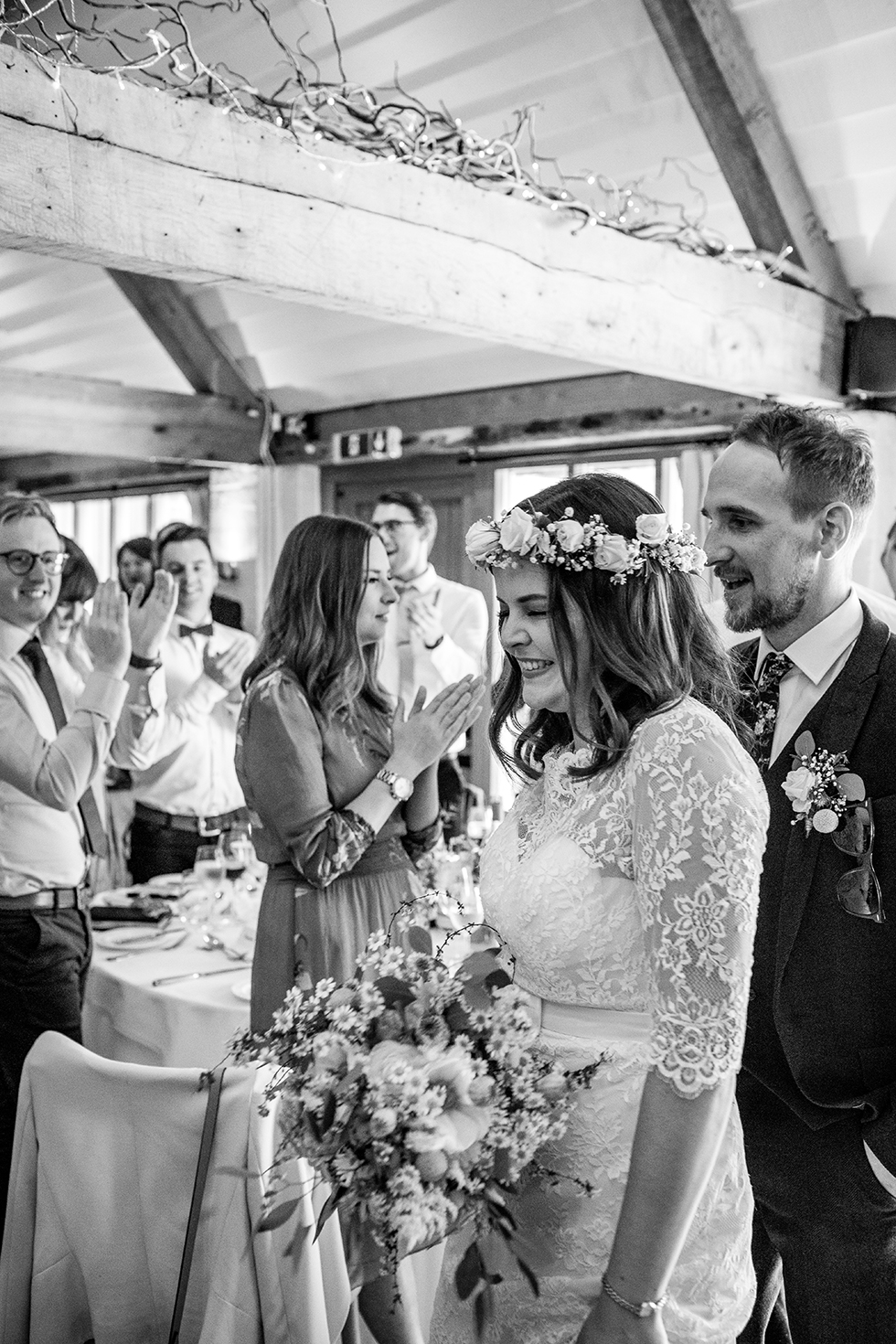 bride and groom walking into their wedding breakfast laughing and having fun