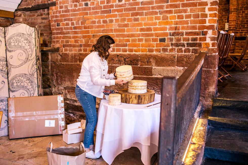 bride setting up wedding cake at Curradine barns