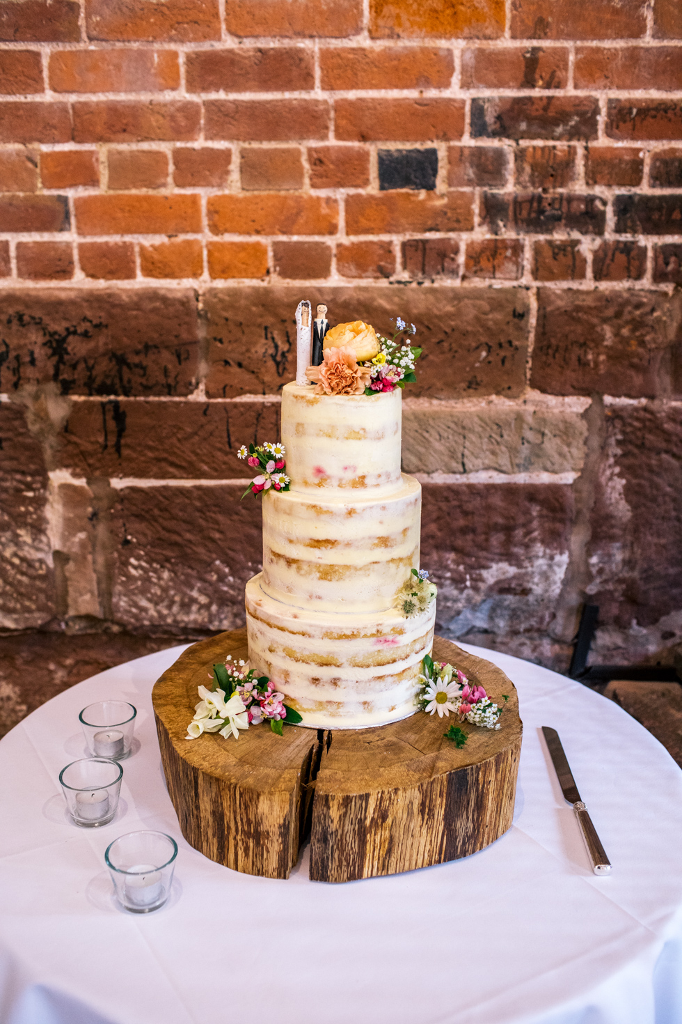 naked 3 tier wedding cake made the bride being setup and decorating with real flowers at the Curradine barns