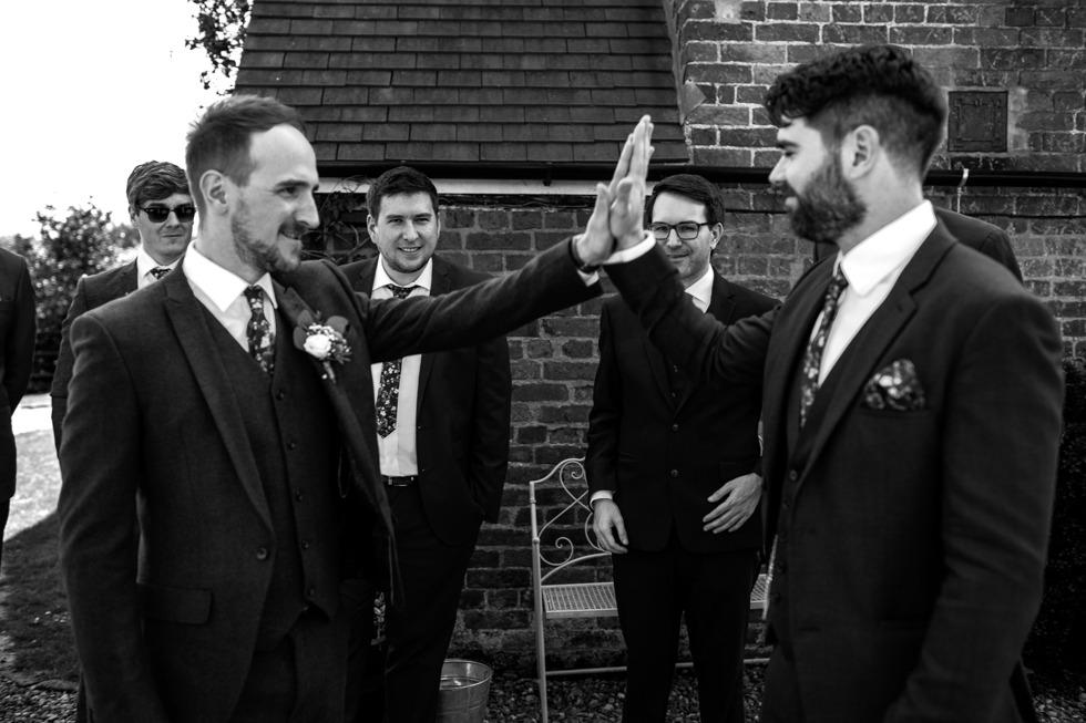groom and best man high five at Curradine barns