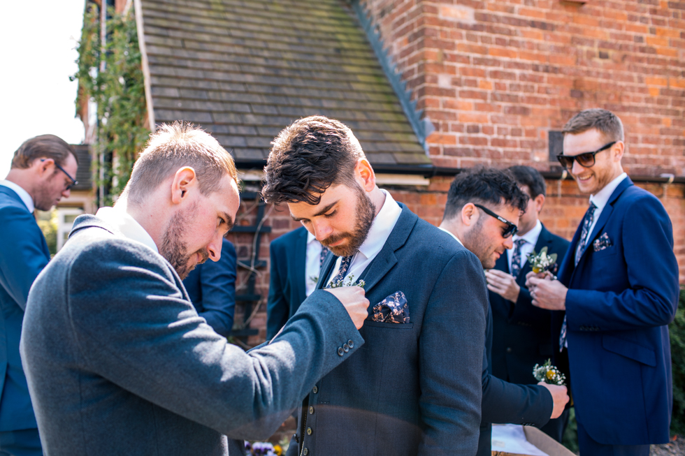 groom helping best man with button hole at Curradine barns