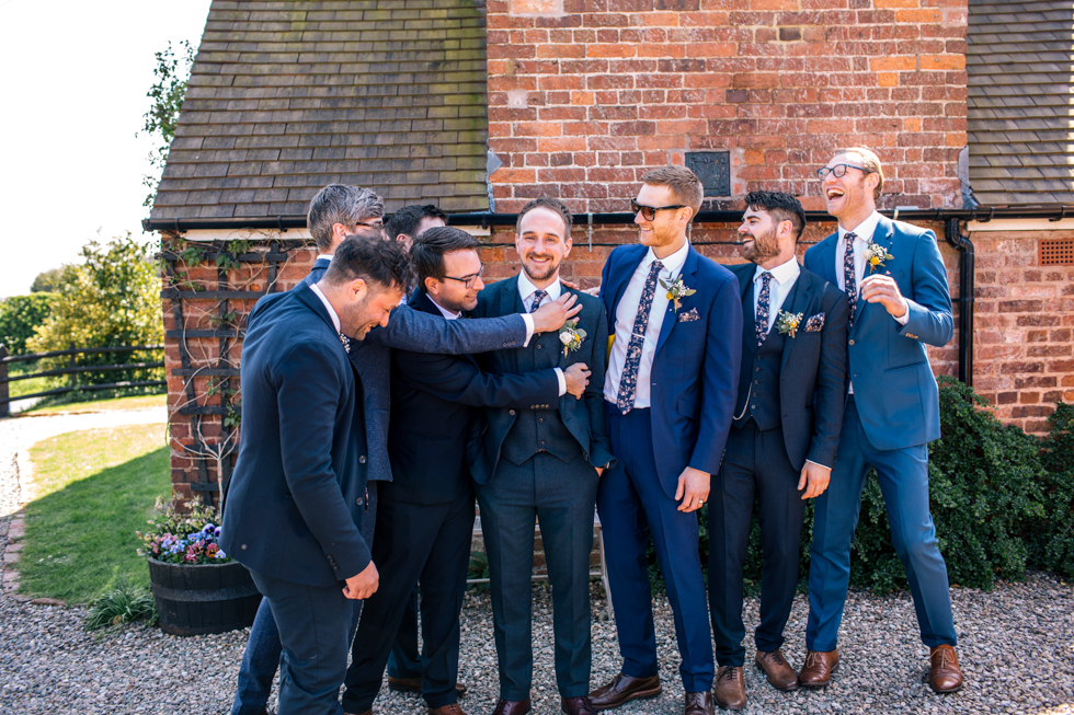 groom and mates messing about next to brick wall at Curradine barns