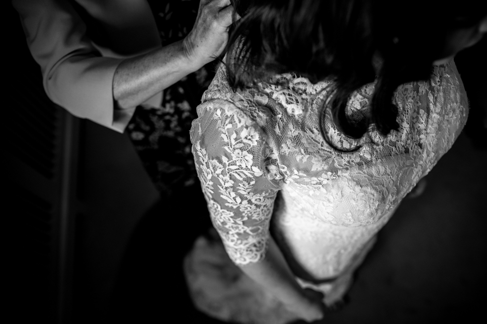 lace wedding dress being buttoned up by brides mum at Curradine barns