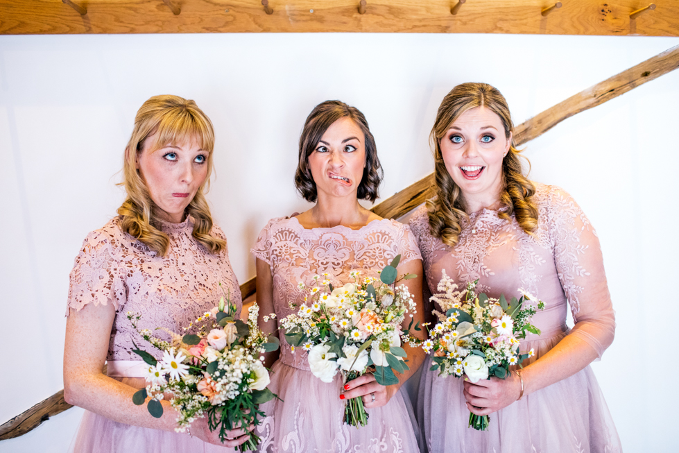 bridesmaids in blush dresses with rustic hand tied wedding flowers