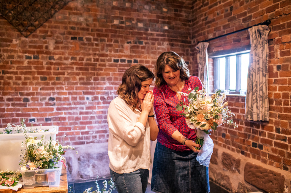 bride crying at first seeing her wedding flowers at the Curradine barns